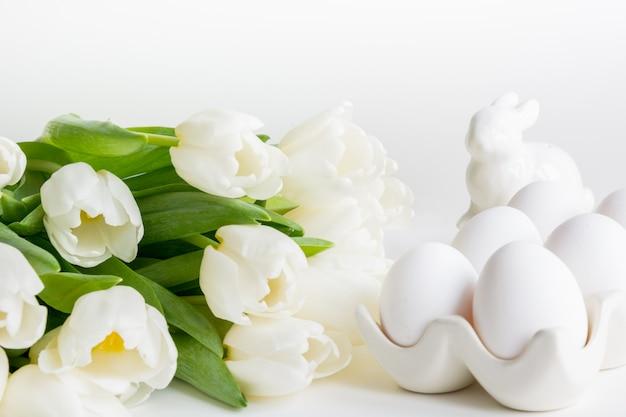 Easter concept. white tulips, nest, eggs on white.