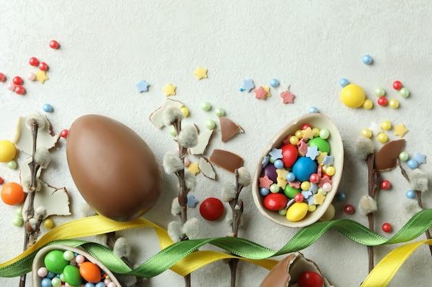 Концепция пасхи с шоколадными яйцами на белой текстурированной стене