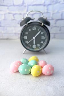 卵とテーブルの上の時計とイースターのコンセプト