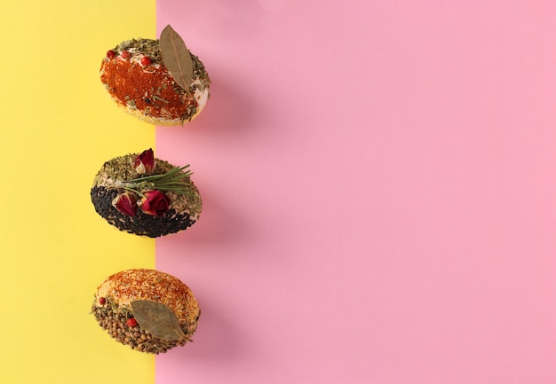 Пасхальная концепция с яйцами, украшенными различными специями и злаками без красителей и консервантов на розовом и желтом фоне, место для текста