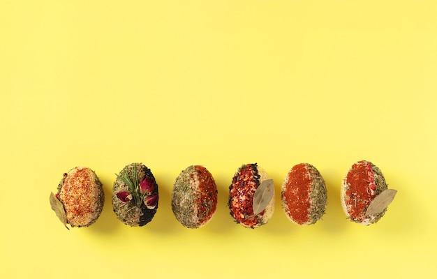 黄色の表面に染料や防腐剤を含まないさまざまなスパイスやシリアルで飾られた卵のイースターコンセプト、テキスト用スペース