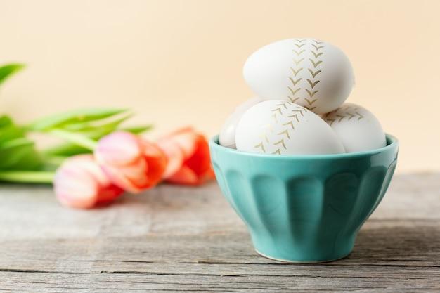 그릇과 튤립에 그려진 계란 부활절 개념