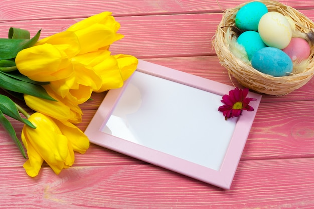 Easter concept. wooden frame with easter eggs and tulips