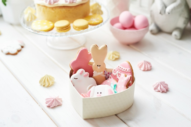 Easter cookies in box and sweet cake with macarons