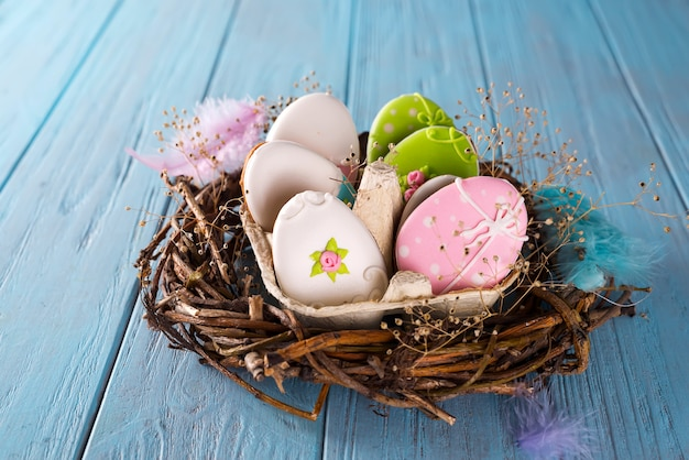 Easter cookies egg in the paper and nest on blue background