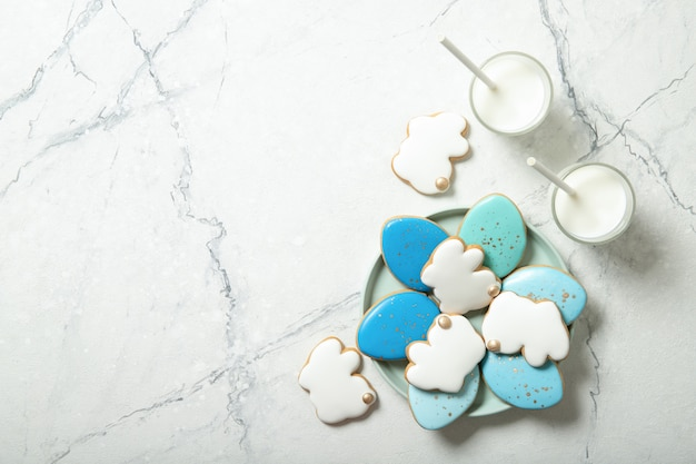 Печенья пасхи в плите на конкретной предпосылке. стакан молока. пасхальные яйца. пасхальные кролики.