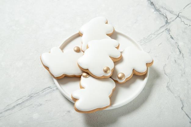 Пасхальное печенье в тарелку на бетонной поверхности. пасхальные кролики. место для текста. вид сверху. крупный план.