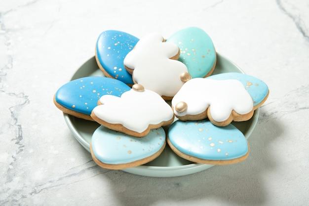 Пасхальное печенье в тарелку на бетонной поверхности. стакан молока. пасхальные яйца. пасхальные кролики. место для текста.