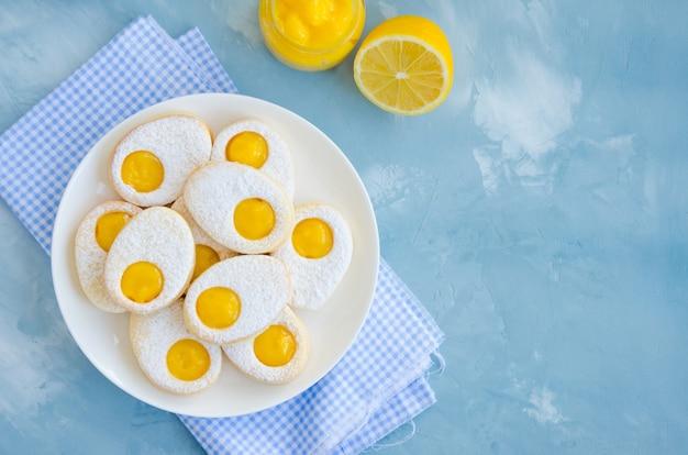 Пасхальное печенье в виде пасхального яйца с сахарной пудрой и лимонным кремом на белой тарелке