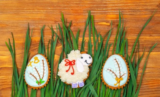 Пасхальное печенье. овцы и пасхальные яйца на зеленой траве