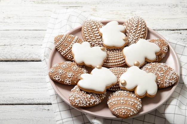 Пасхальное печенье на тарелку на деревянном фоне. пасхальные кролики. пасхальные яйца