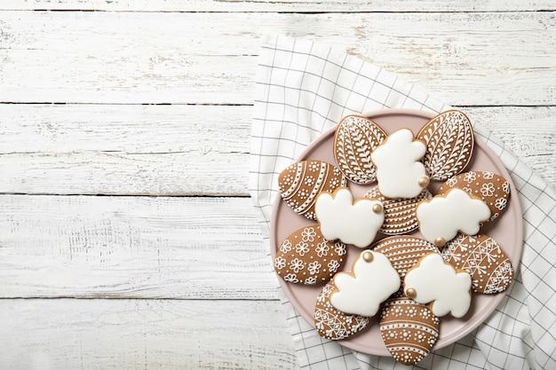 Пасхальное печенье на тарелку на деревянном фоне. пасхальные кролики. место для текста. пасхальные яйца