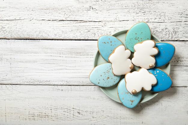 Пасхальное печенье на тарелку на деревянном фоне. пасхальные яйца. пасхальные кролики. место для текста.