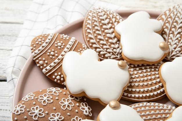 Пасхальное печенье на тарелку на деревянной поверхности. пасхальные кролики. пасхальные яйца