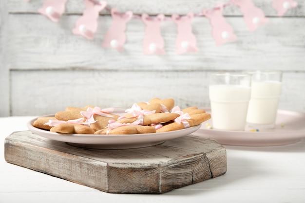 Печенья пасхи на плите с стеклом молока на деревянной поверхности. пасхальные кролики. пасхальные гирлянды.