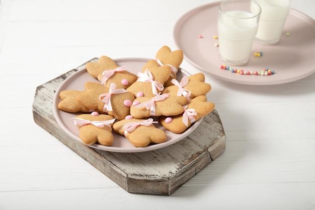 Печенья пасхи на плите с стеклом молока на деревянной поверхности. пасхальные кролики.