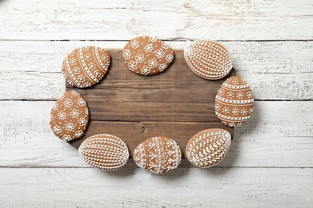 白い木製の背景にイースタークッキー。テキストのための場所。イースターエッグ。フレームの形。