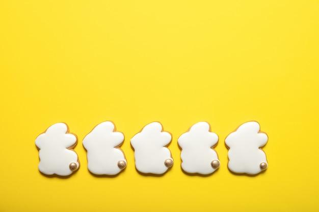 Пасхальное печенье на желтом фоне. пасхальные кролики. вид сверху. место для текста.