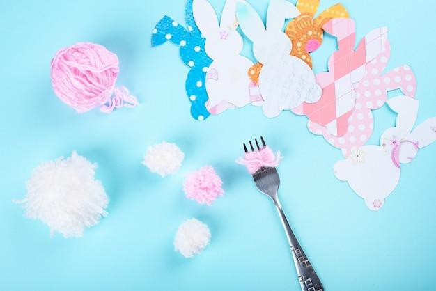 포크로 원사 pom pom 토끼 꼬리를 만드는 부활절 공예. 부활절 콘텐츠