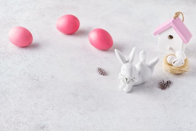 かわいいウサギ、巣、色付きの卵とイースターの創造的なレイアウト。