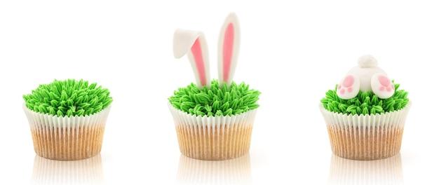 白で隔離のイースターカップケーキ。草、バニーのお尻と耳。