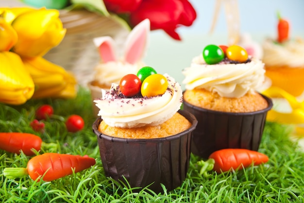 Easter cupcakes with candy eggs, colorful eggs on a festive table