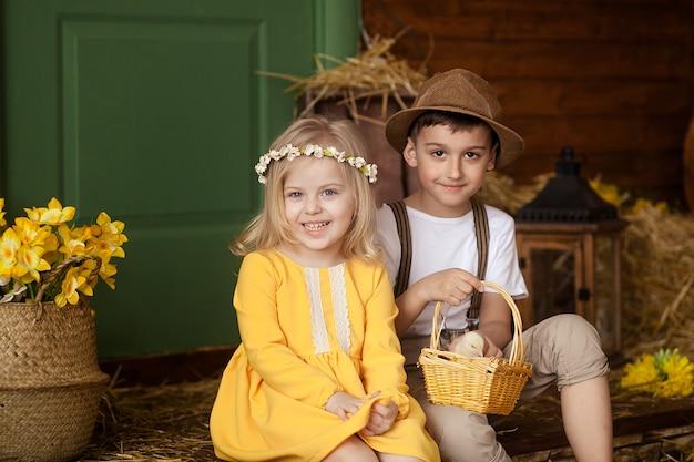 イースター!かわいい小さな幸せな子供たち、動物と干し草の中で男の子と女の子-イースターの日に鶏とウサギ。子供たちは楽しんで、遊んで、抱きしめています。