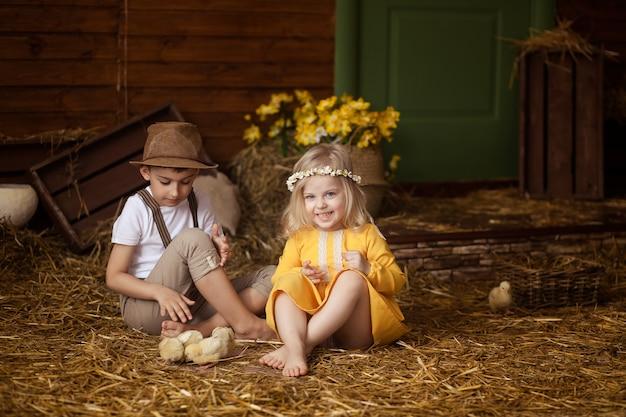 イースター!かわいい小さな幸せな子供たち、動物と干し草の中で男の子と女の子-イースターの日に鶏とウサギ。