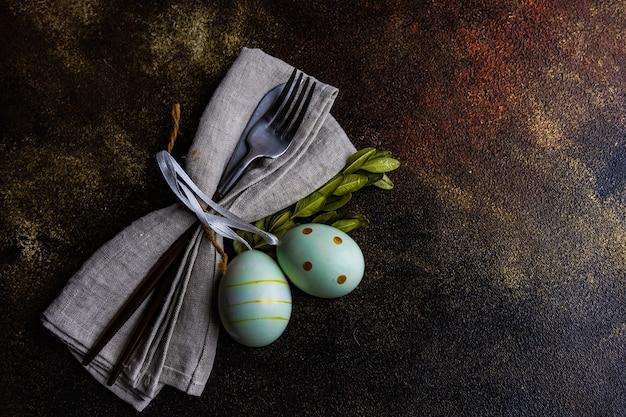 색된 계란과 회양목 부활절 칼 설정 콘크리트에 나뭇잎
