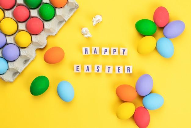 イースターの日黄色の背景に飾られた卵と小さなウサギ