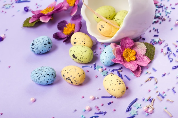 Easter decor in pastel colors. easter eggs, candy, sweets, flowers and eggshells.
