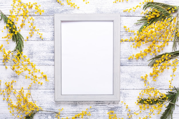 Easter decor with mimosa flowers and frame on wooden background