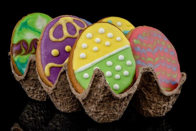 Пасха украшенные запеченные яйца, печенье на черном фоне.