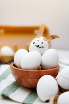 Easter, decorated egg with rabbit face and other white eggs in wooden bowl and egg tray on green and white striped cloth