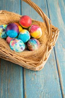 Пасхальные яйца в корзине на сене на бирюзовом деревянном фоне.