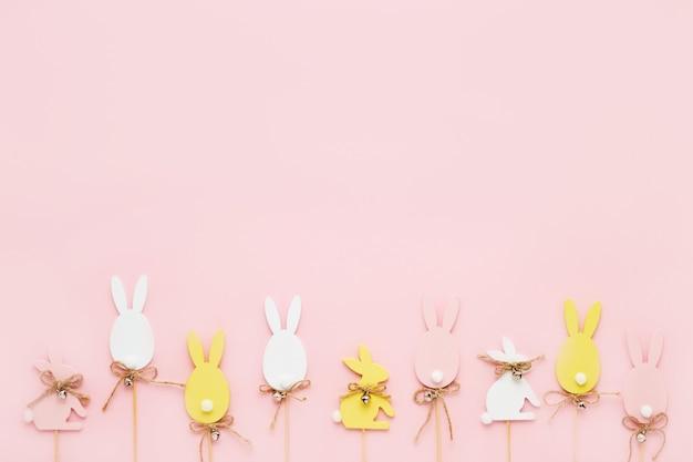 イースターの装飾。ピンクの背景にカラフルな木製のイースターエッグとバニー。