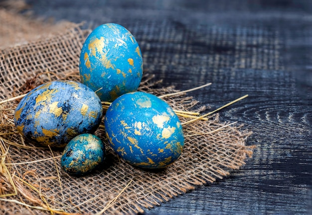 Easter decoration concept blue painted eggs on the sackcloth with hay closeup on dark background