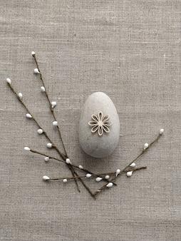 리넨 면 배경에 자갈 바위와 버드나무 나뭇가지에서 부활절 장식. 플라스틱 없는 컨셉과 제로 웨이스트