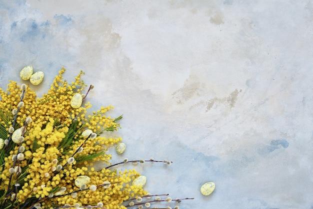 Пасхальное украшение, цветы вербы и мимозы на синем фоне. копирование пространства, вид сверху. концепция празднования пасхи.