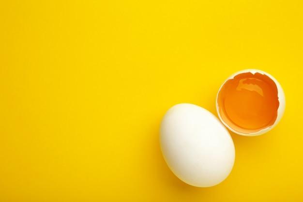 Пасхальные украшения белые яйца на желтой стене, минимальный дизайн с пространством для текста. вид сверху