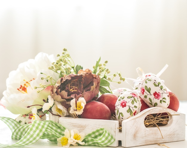 Easter decoration with a basket and red eggs with flowers