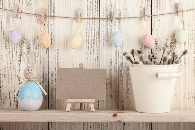 Easter decoration with blank card on wooden background