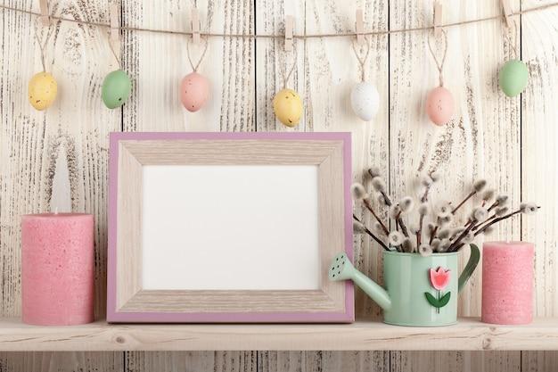 棚の上の空白の木製フレームとイースターの装飾