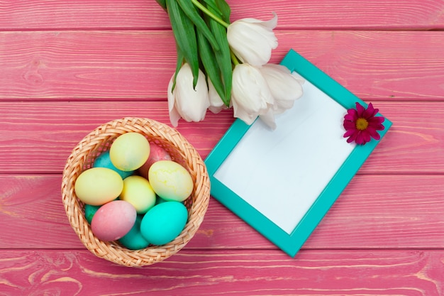 Easter decoration with tulips, eggs and blank frame. top view