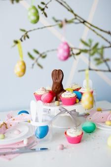 Пасхальные украшения - украшенный стол с кексами, красочные расписные пасхальные яйца и шоколадный кролик.