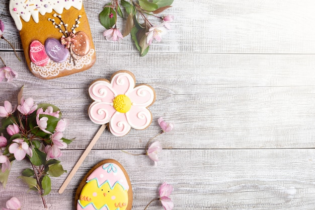 Easter decorations laid out on wooden table. pink apple tree branches, gingerbreads as easter cake, flower and egg.