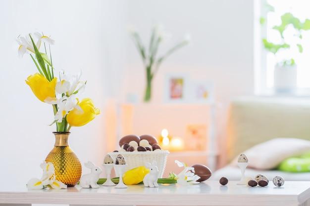 白いインテリアの春の花とイースターの装飾