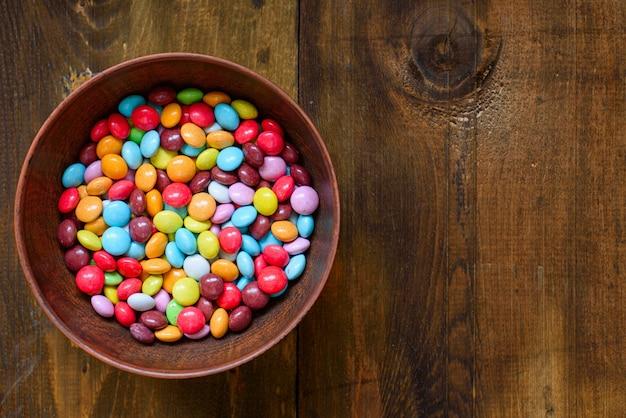 어두운 나무 테이블에 그릇에 부활절 디저트 다채로운 사탕 당의. 공간 복사