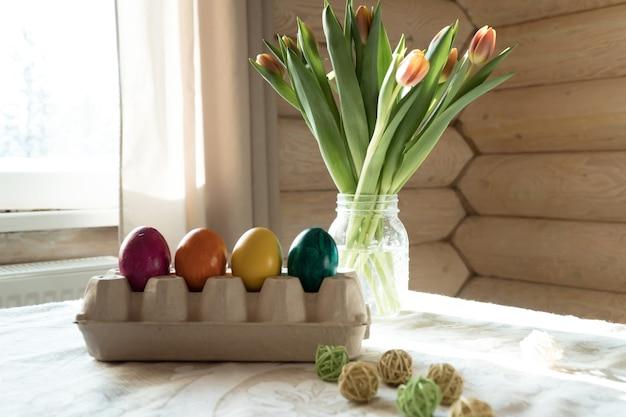 Украшение пасхального обеденного стола разноцветными яйцами и тюльпанами в загородном доме
