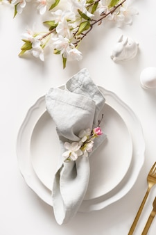 Easter dinner with blossom flowers on white table, spring and blooming decoration.